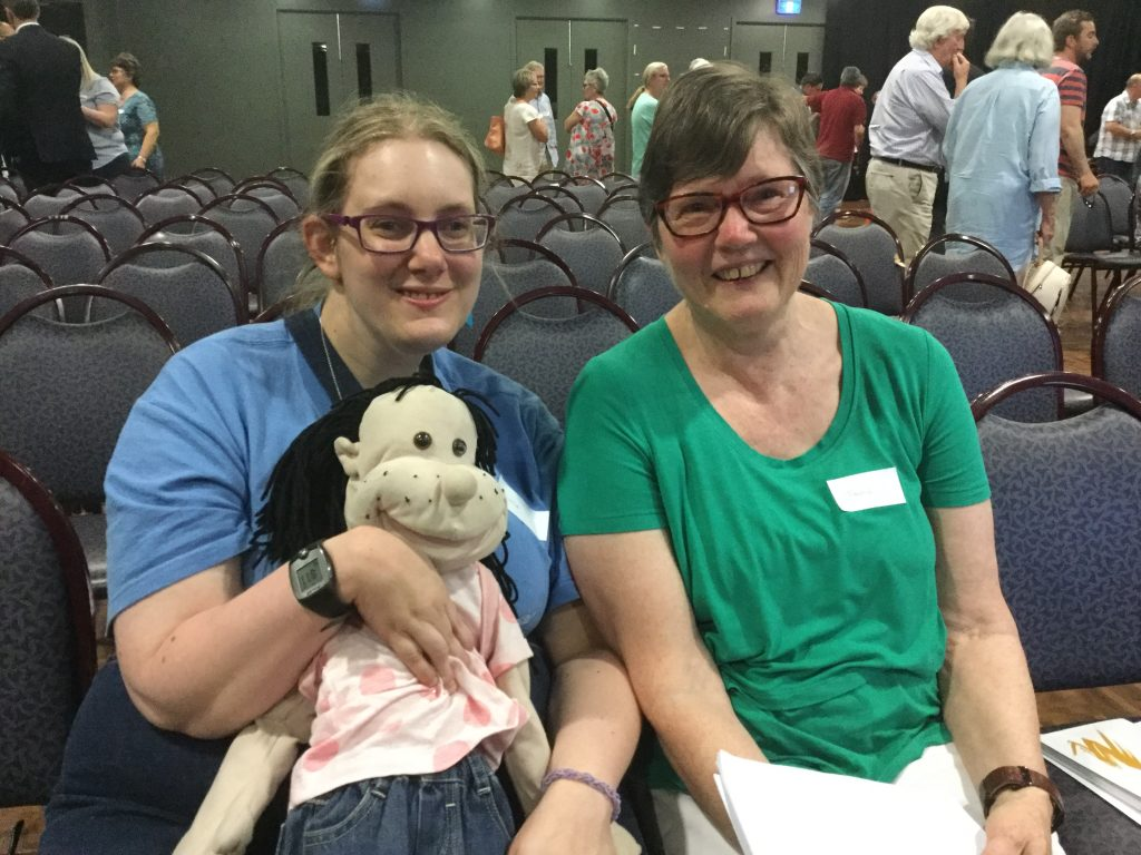 Participant holding a doll, sitting with mother, both wearing glasses and smiling