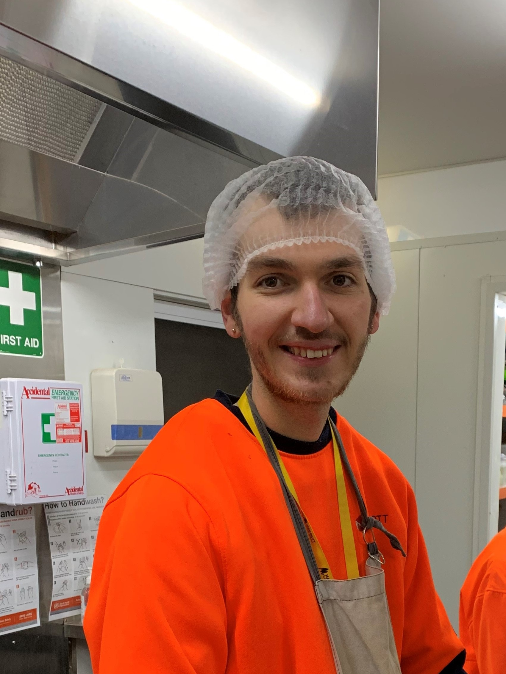 Employee with a disability smiling with a hair net on head in a kitchen