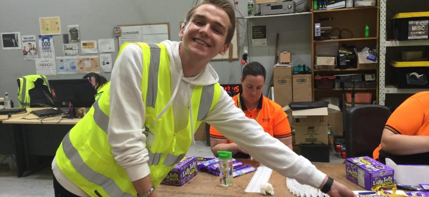 young corporate nab volunteer reaching across table, packing, marriott industries