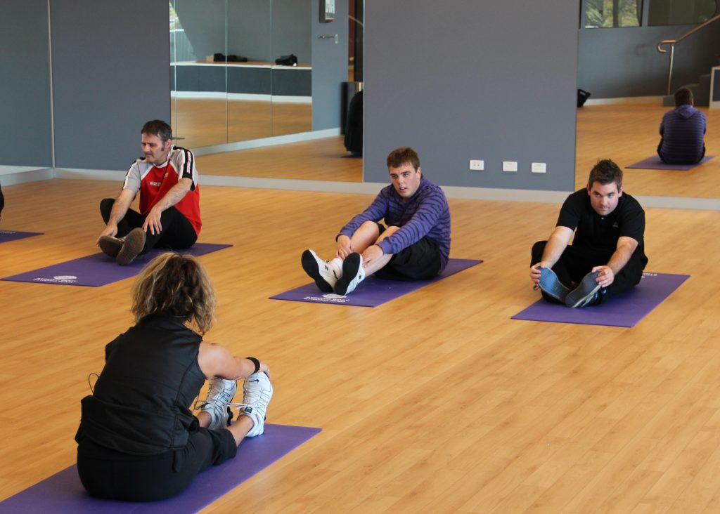 three people stretching in a yoga class looking forward at the yoga instructor