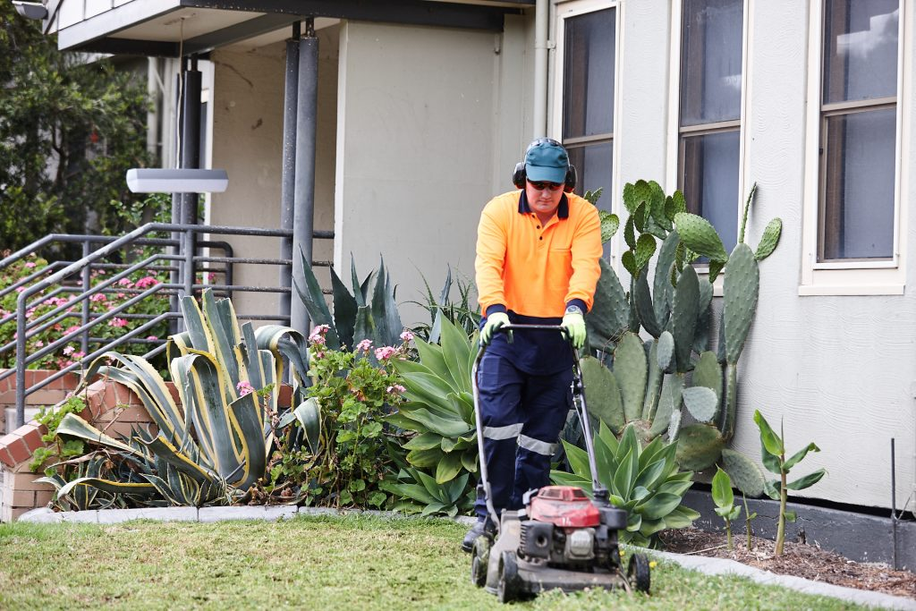 Person with a disability wearing a yellow high vis long sleeve shirt, blue pants, moving a lawn
