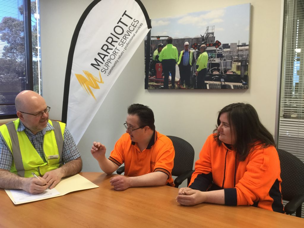 Male Staff member in yellow his vis jacket talking with male and woman supported employees
