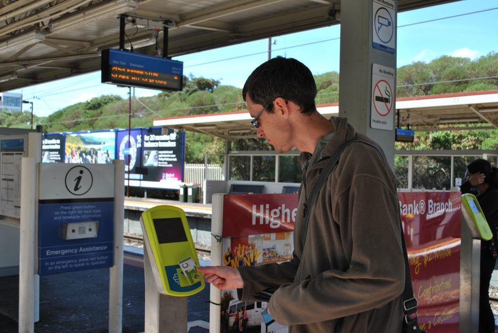 Person with a disability wearing a dark green jumper at a train station tapping their myki card