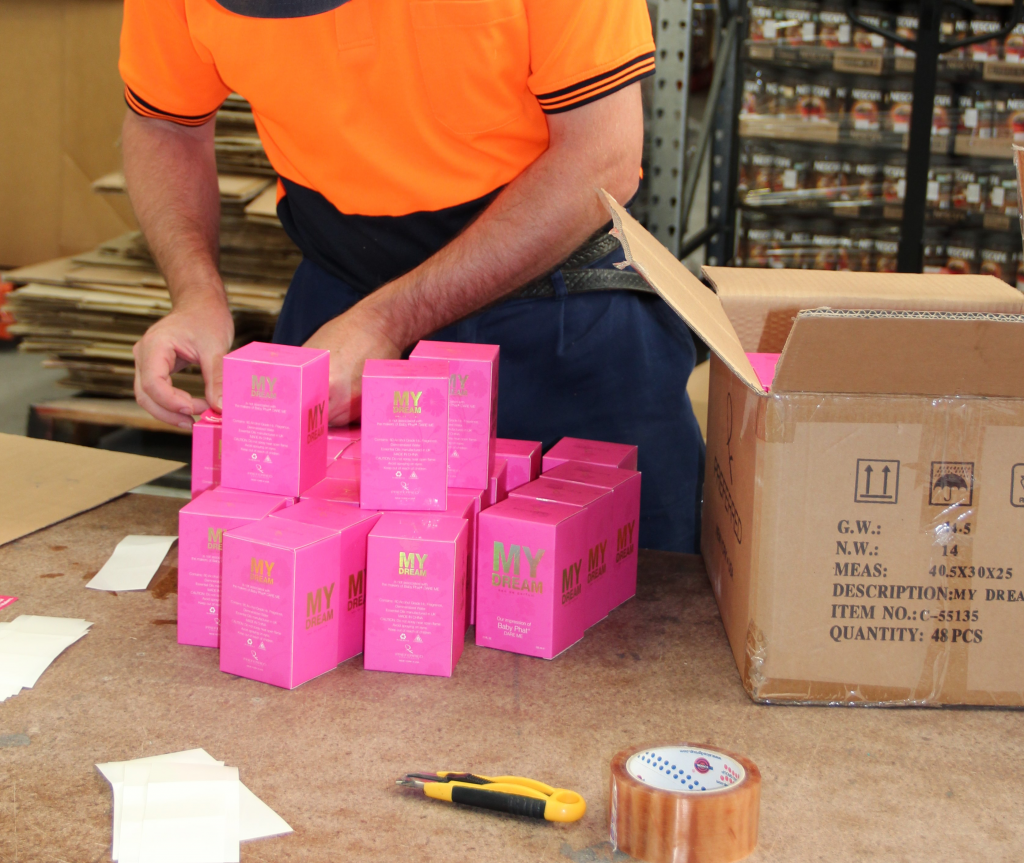 Person with a disability wearing an orange hi vis vest putting labels on pink boxes
