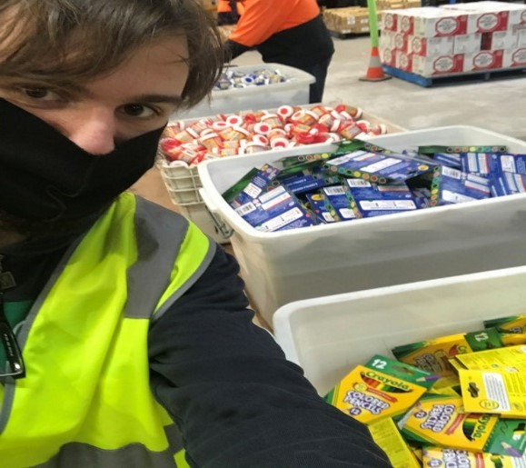 Brown haired, young man in a hi vis vest, wearing a black face mask,packing crayons and pens