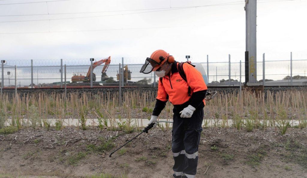 Person wearing personal protective equipment spraying the ground for weeds in front of train tracks