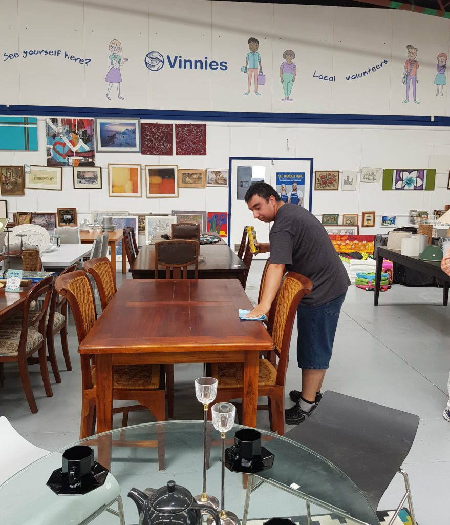 Person with a disability wiping down a table made of wood at a Vinnies charity store