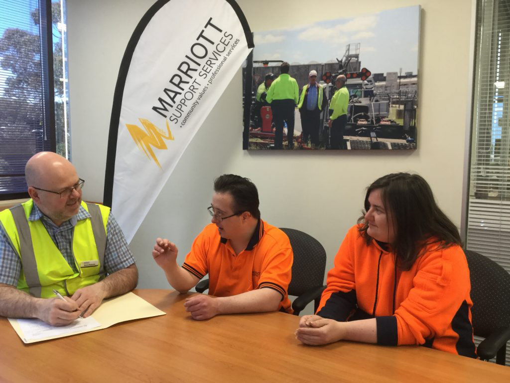 Staff member speaking with two supported employees