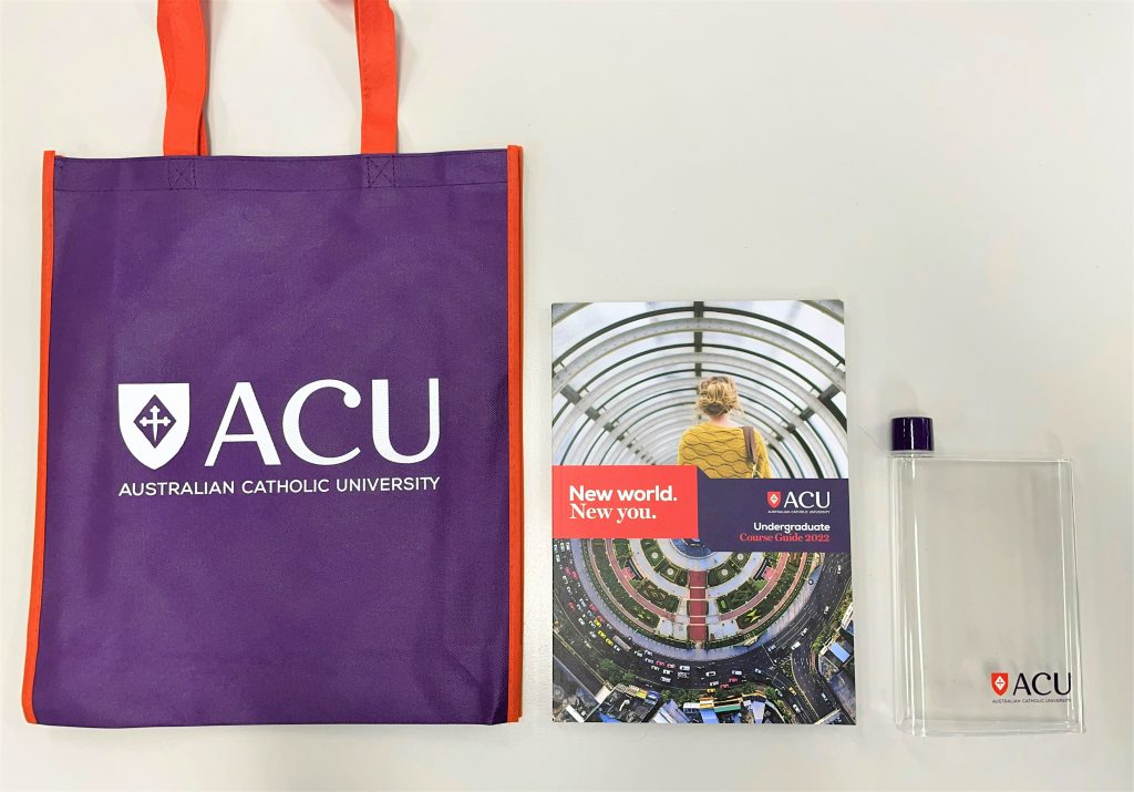 Australia Catholic University open day bags containing a purple bag with ACU spelt out, a book showing a woman with blonde hair's back, a clear square drink bottle with ACU logo on it
