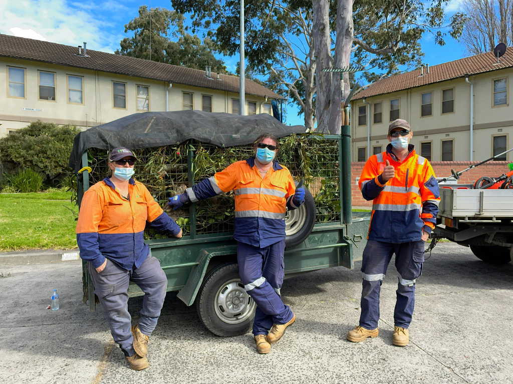 A woman standing next to two men holding their thumbs up wearing face masks and hi vis gardening uniform