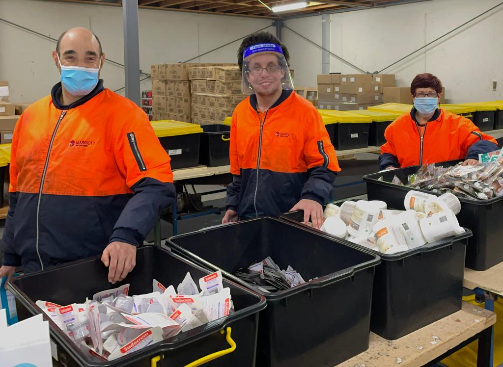 Three Industries employees wearing orange hi-vis uniform, pick packing Bounty Bags