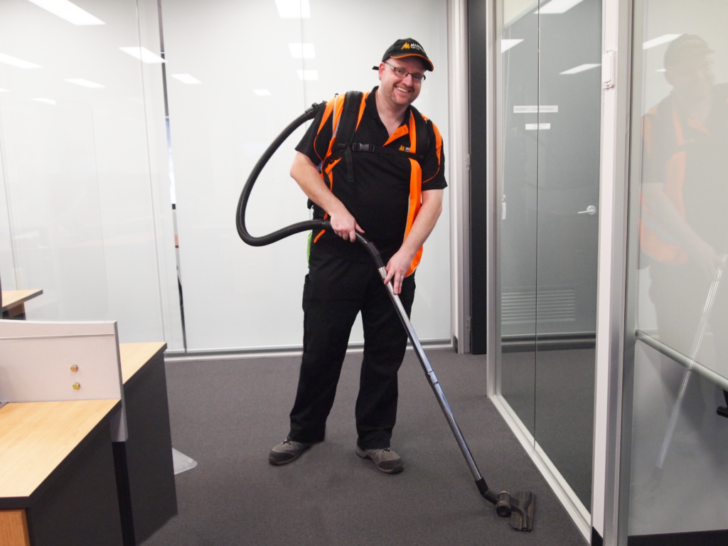 Tall man wearing glasses and smiling whilst vacuuming an office space
